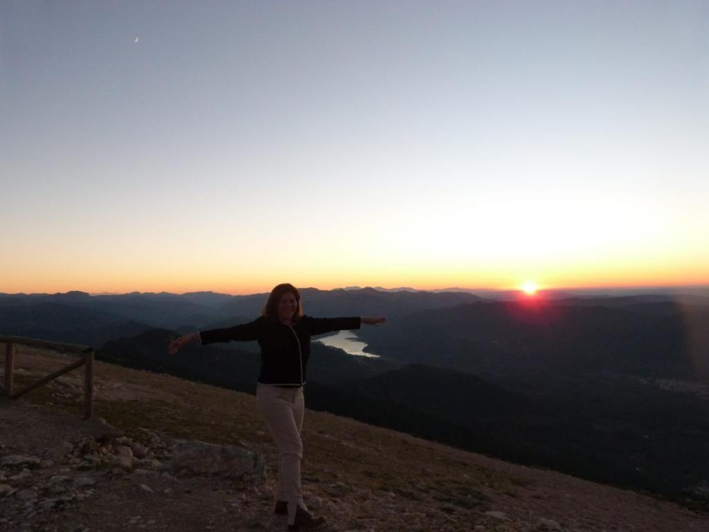 Mulher feliz com os braços abertos de fundo uma paisajem montanhosa linda.